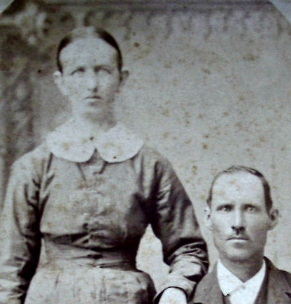 Close up of man and woman in old family photograph from 1883. Woman has hair parted in middle and man with high forehead and hair parted on left.