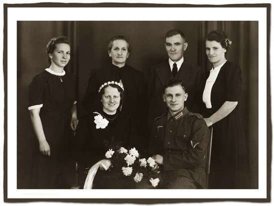 Black and white photo of bride and groom sitting and bride holding bouquet and parent behind them.