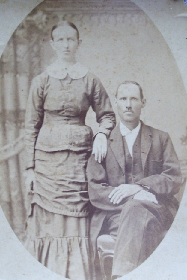 1883 black and white photo of Clara and William Haley. Clara is standing with hand on William shoulder. William is sitting.