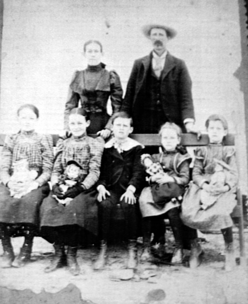 1890's black and white photo of Haley family with parents standing in back and 5 children sitting. William Haley changed his name.
