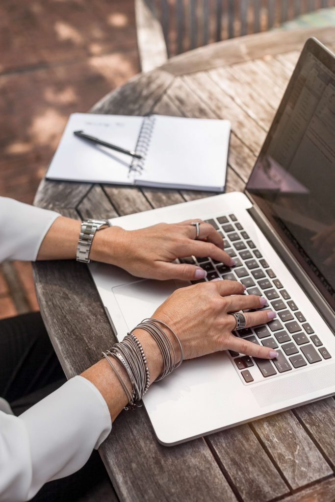 Woman's hands on keyboard of laptop sitting at wooden table