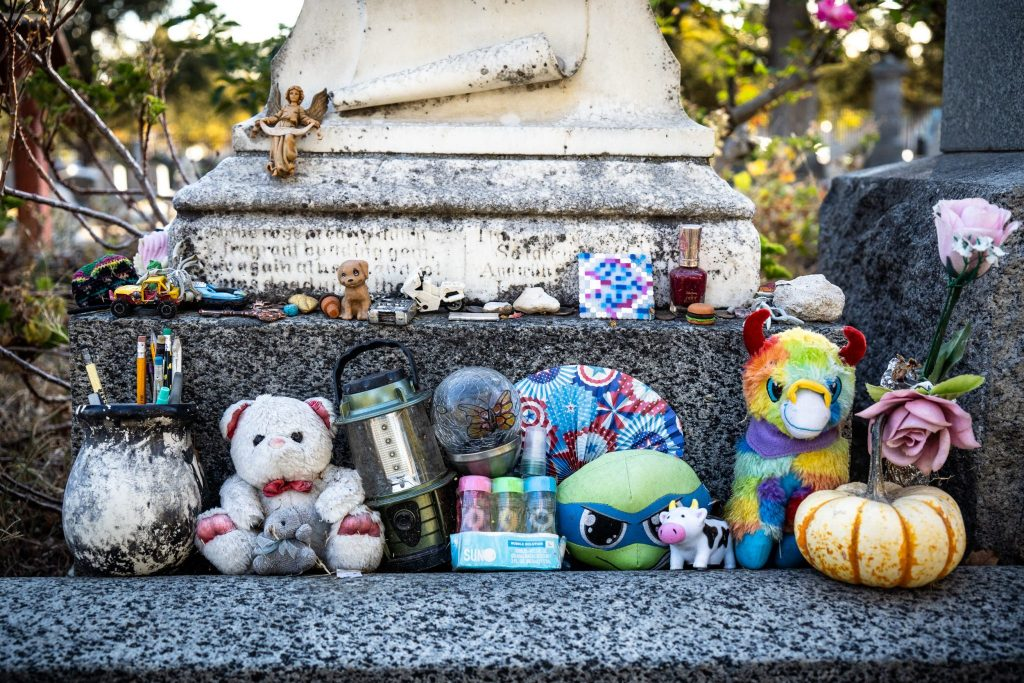 stuffed animals on gravestone while photographing cemeteries