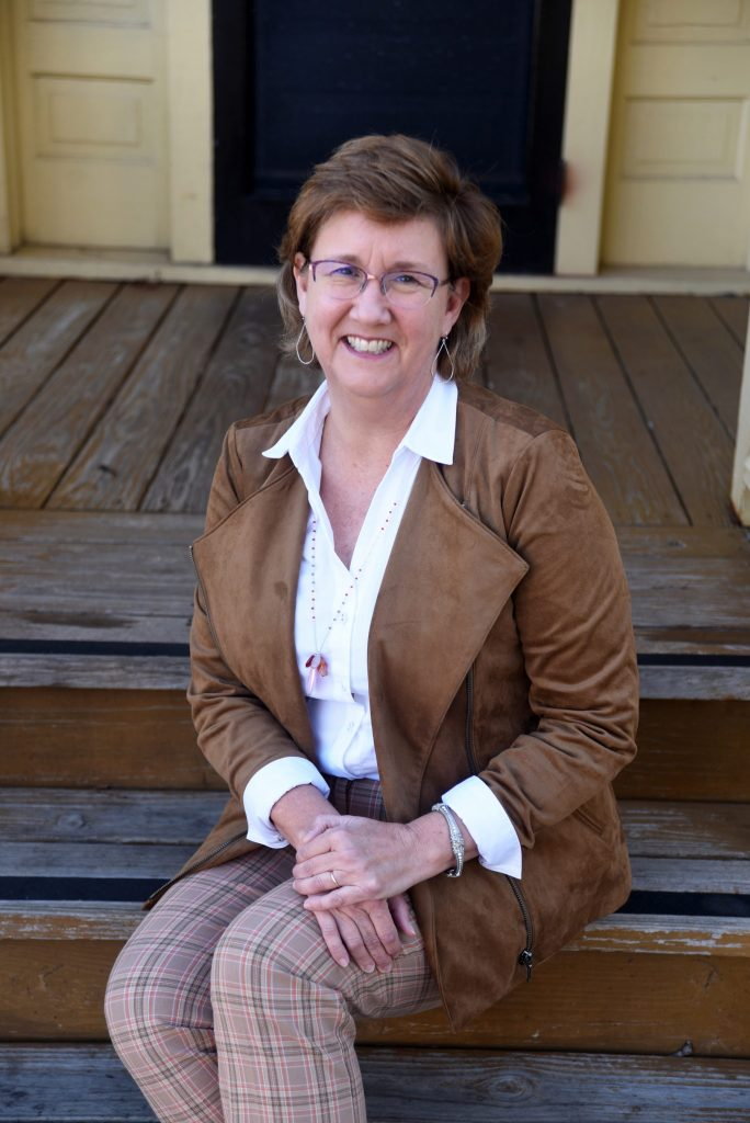 lisa lisson with short brown hair, eyeglasses wearing white shirt  and brown jacket sitting on old wooden steps