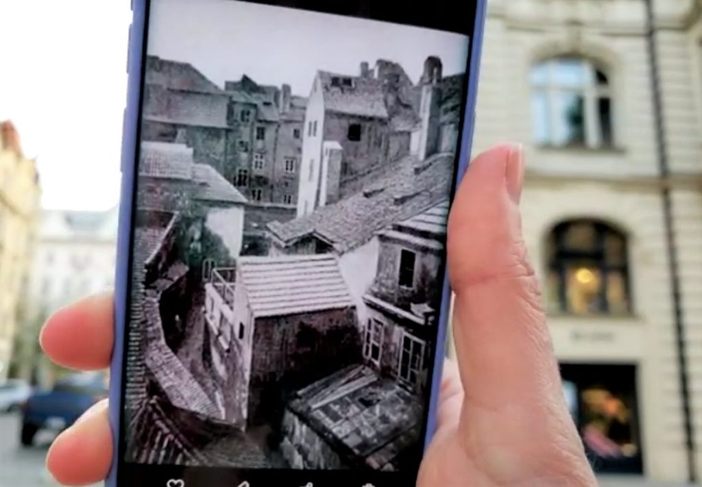 Hand holding cell phone with photo of 1940's Prague Jewish Quarter