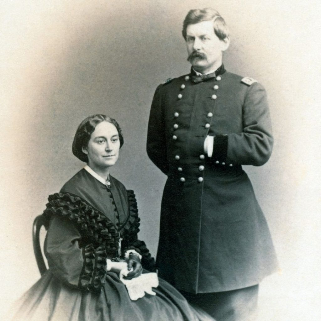 black and white carte de visite with seated woman and standing man in 1860's military uniform. Woman in hoop skirt