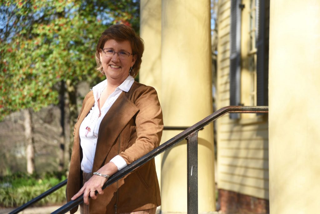 brown haired woman in brown jacket standing on steps of old home