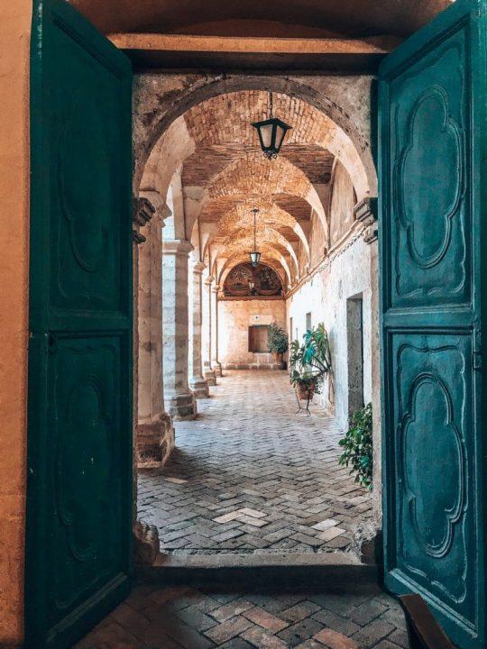 looking through blue door to ornate brick hjallway