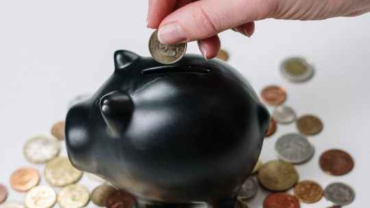 person dropping coins into black piggy bank