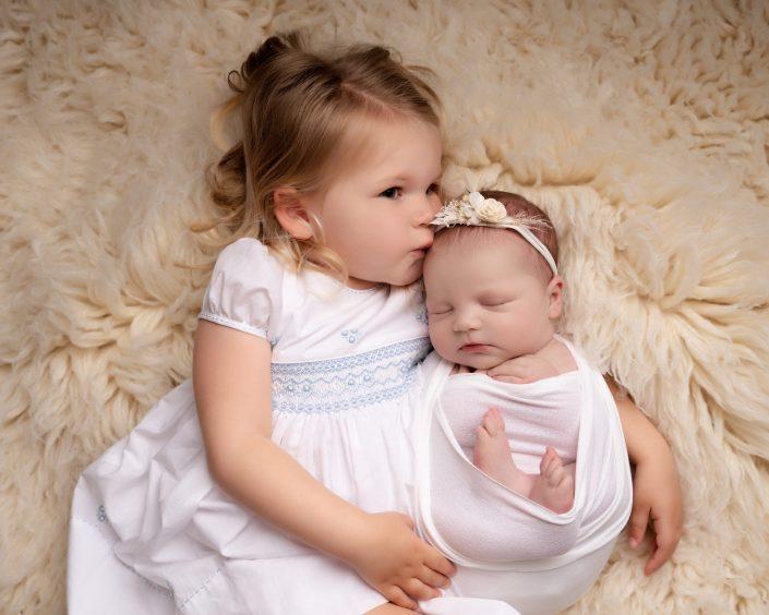 Newborn baby and sibling sister