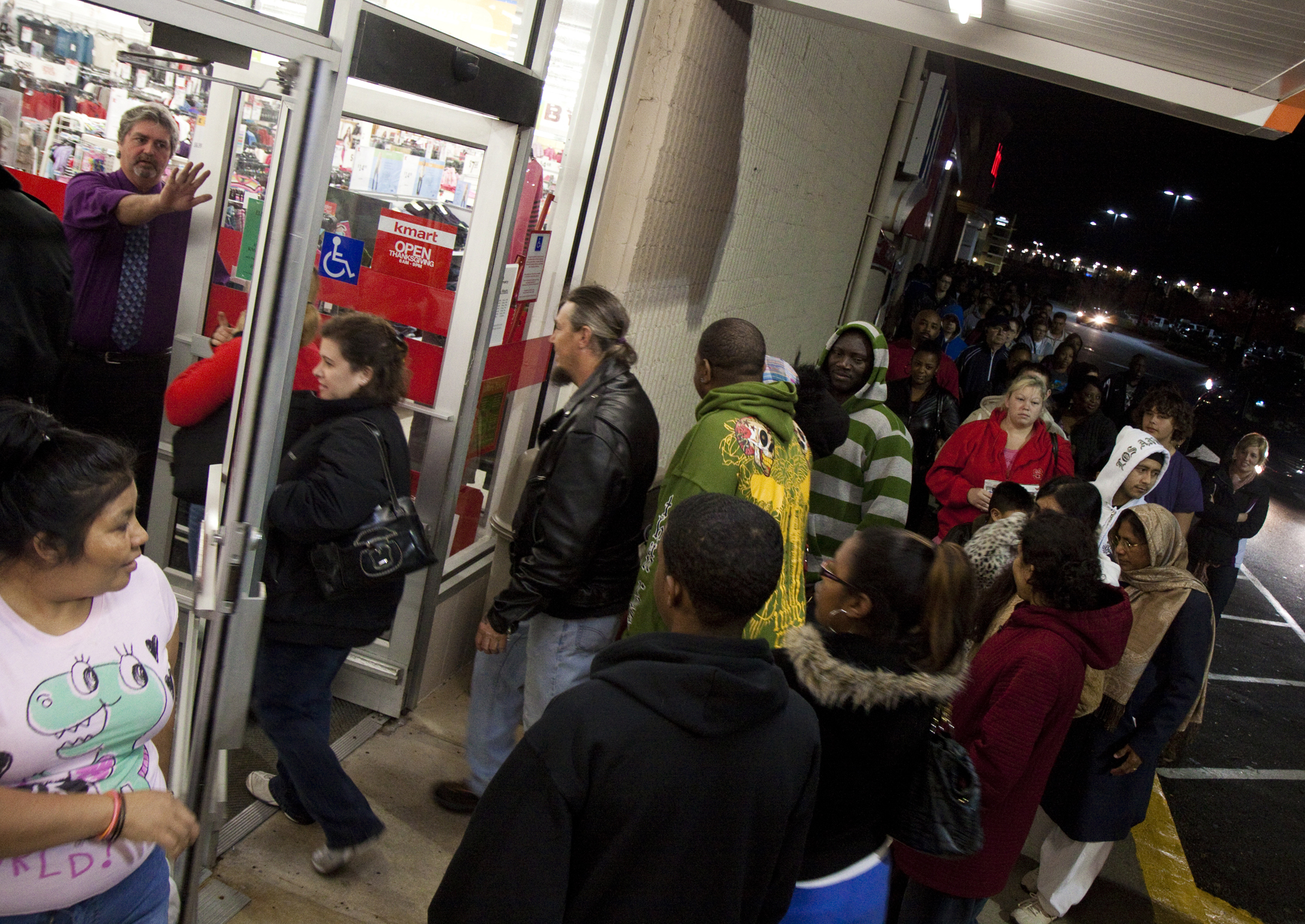 A Big Kmart manager stops Black Friday shoppers from cutting in line as the store opens its doors at 5 a.m. The first shoppers arrived at 11:15 p.m. the night before to get deals on TVs and DVD players.
