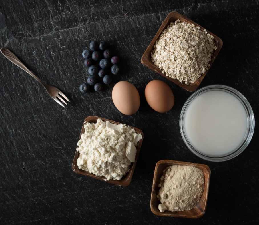 Zutaten für Protein-Kaiserschmarrn: Haferflocken, Kokosdrink, Eier, Kokosmehl, Proteinpulver, Heidelbeeren und Backpulver