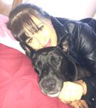Lisa hugging sleepy dog indoors and smiling