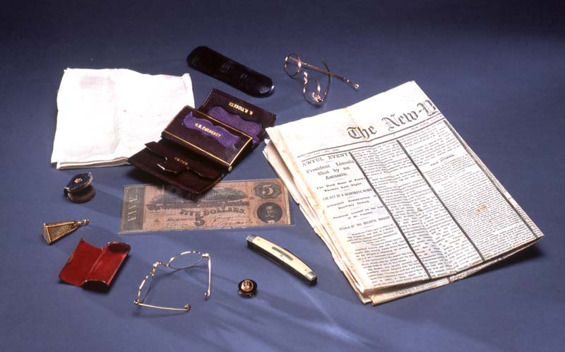 Lincoln assassination artifacts: contents of Lincoln's pockets the night he was murdered (left) and copy of a newspaper announcing the assassination (right)