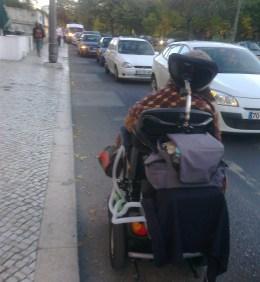 Foto de Raquel Rodrigues a deslocar-se pela estrada na sua cadeira de rodas devido à falta de passeio rebaixado.