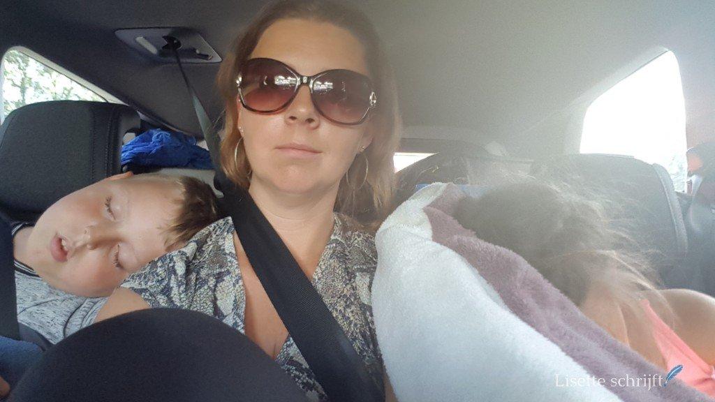 moeder in de auto met twee kinderen