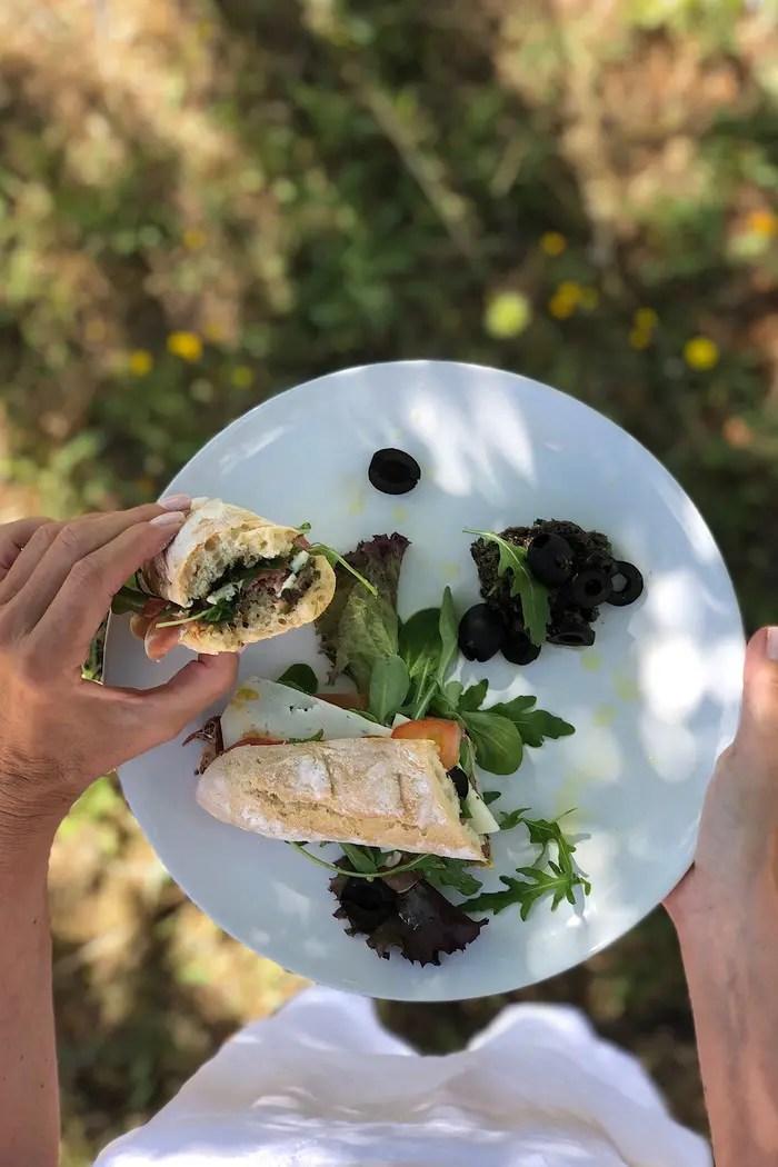 Mediterranes Sandwich aus frisch gebackenem Baguette mit selbstgemachter Olivenpaste