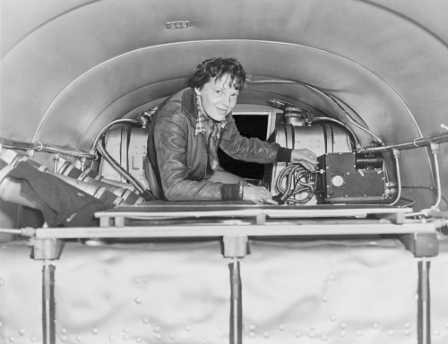 Amelia Earhart checking over equipment in her plane