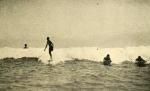 Jack London standing up on a surfboard at Waikiki Beach