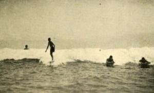 Jack London standing up on a surfboard at Waikiki Beach