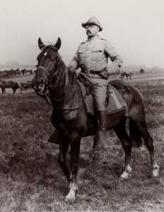 """Theodore Roosevelt on horseback leading his """"Rough Riders"""" in Cuba"""