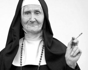 Nun Smoking Cigarette --- Image by © Norbert Schaefer/Corbis