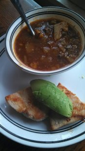 vegetable beef soup and chicken breast with avocado on top