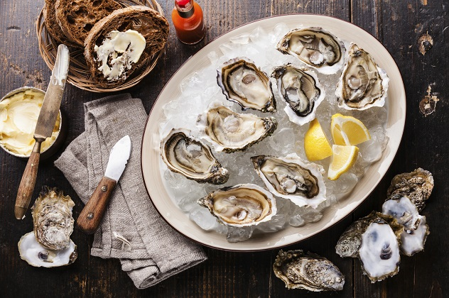 Opened Oysters on plate and dark bread with butter on dark wooden background