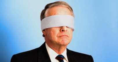 A senior businessman with a blindfold on.