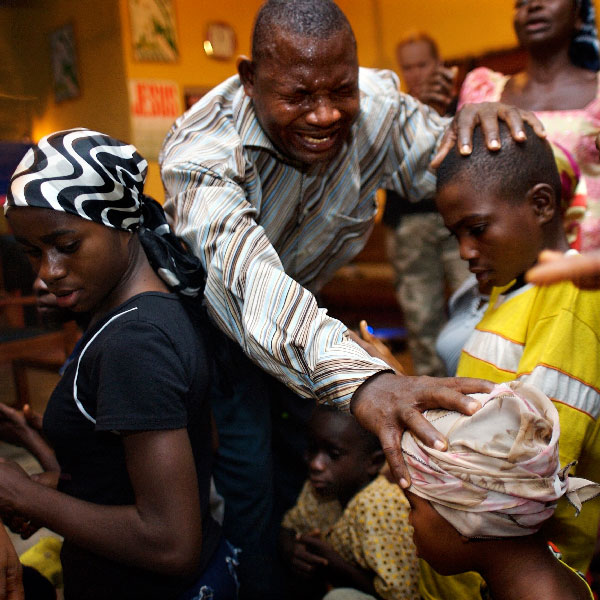 Pastor praying for a child accused of witchcraft