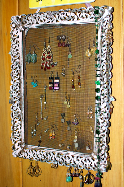 Earrings hanging on a framed piece of mesh wire