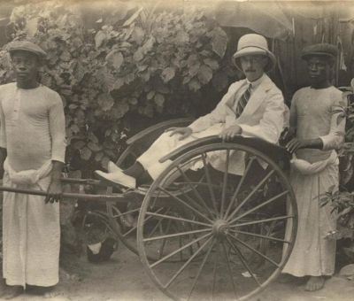 Osborne in a rickshaw, with boys besides him, Lagos c.1910-13. Source: Wikimedia Commons