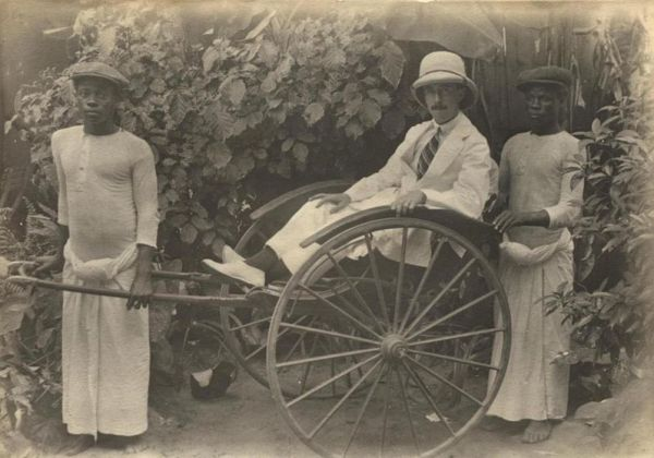Osborne in a rickshaw, with boys besides him, Lagos c.1910-13