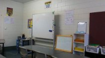 A small turn from the previous image and you can see the main teaching whiteboard, our lesson focus board and the shelves storing student folders.