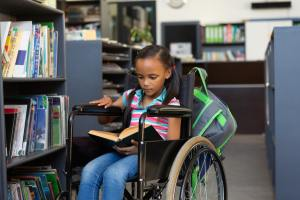 Front view of a disabled mixed-race schoolgirl reading a book in the library at school