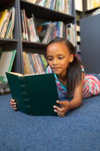 Front view of a mixed-race schoolgirl reading a book in the library at school