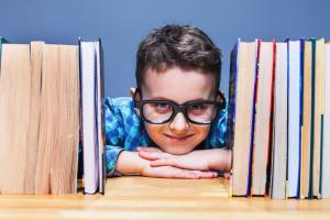 Happy pupil in glasses against books