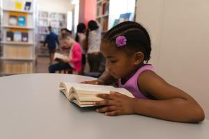 Side view of schoolgirl reading book at table in in school library