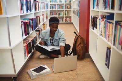 Schoolgirl sitting on floor and doing homework in library
