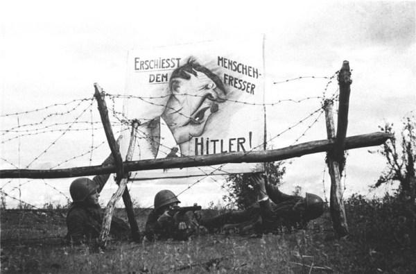 Красноармейцы вывешивают карикатуру на Гитлера на передовой линии фронта