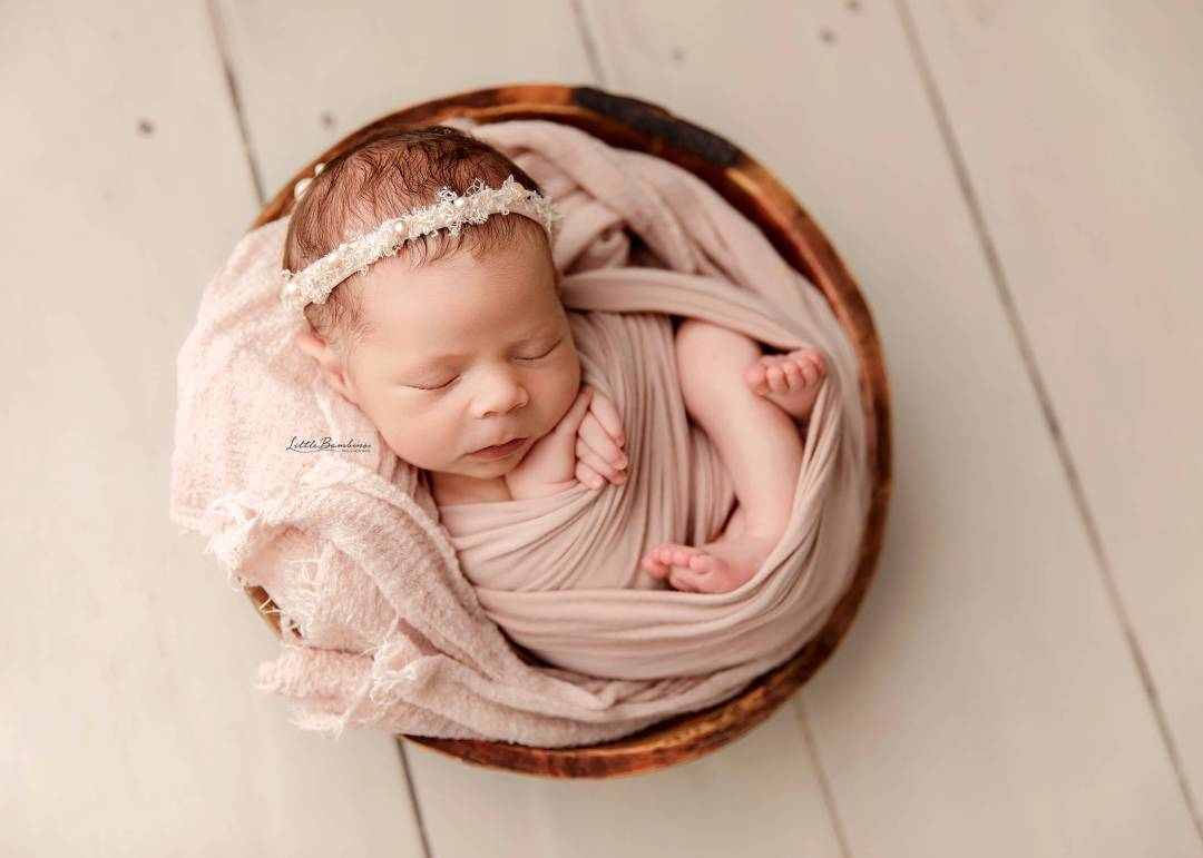 baby girl in pink bowl curled up photograph