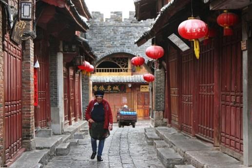 Frau in Naxi-Tracht geht am frühen Morgen durch die Gassen von Lijiang Old Town