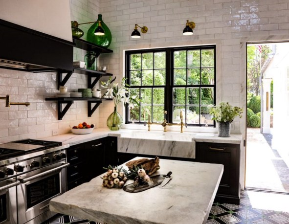 nbcnewyork  Black Kitchen with stainless steel range and brass sink faucets