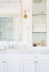 Studio McGee Bathroom with Glass Shelf Tower Brass lighting and chrome faucets