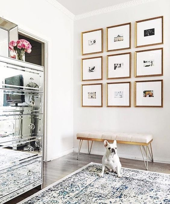 frame bridge bedroom with chrome mirrored chest and gold framed gallery wall