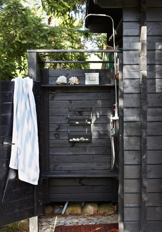 dark wood outdoor shower with pebble floor