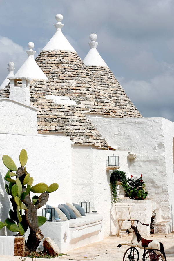 via conde nast white stucco  home with stone cone roofs