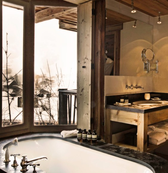 rustic bathroom with oval soaking tub with black marble deck