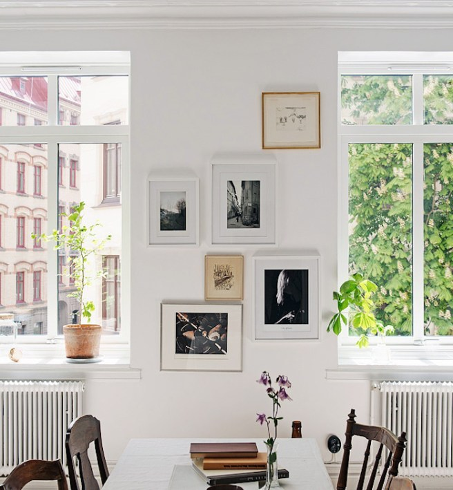 White Walls, Dual Windows with Transoms, Dual White Painted Radiators, Gallery Wall Art, Window Seal Plants, Mixed Vintage Wood Chairs, White Breakfast Nook Table