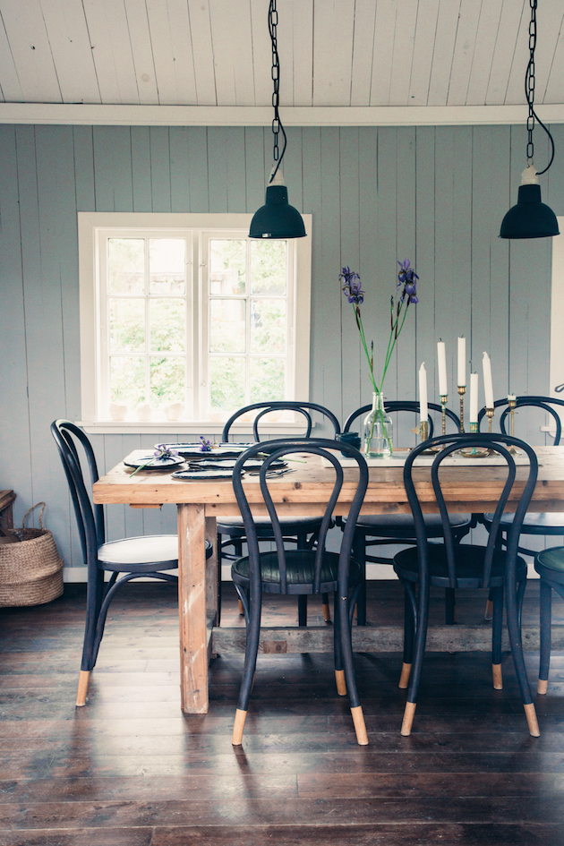 Farmhouse Dining Room with Moody Blue Wood Plank Walls, Rustic Distressed Farm Table, Black Wood Rattan Chairs with Exposed Natural Maple Legs, Woven Market Baskets