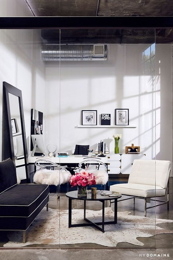 my domaine white lacquered desk and credenza, home office behind glass partition, hide area rug in office area, acrylic chairs with sheep skin throws